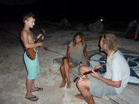Tom s'essaie à la guitare (de forme plutôt originale) de voyageurs rencontrés