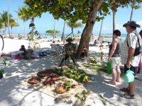 Artisan qui fabrique des paniers, des chapeaux ou mobiles avec des feuilles de cocotiers tressées