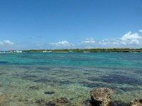 Paisible lagon où dort tranquillement Coco d'îles, au loin