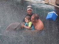 Même la pluie battante ne le pertube pas pour faire un bisou à son dauphin