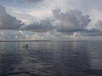 Un pêcheur sur l'eau paisible du petit jour